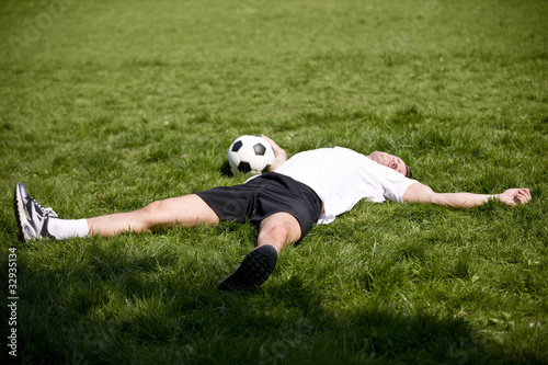 A young man lying on the grass, holding a football