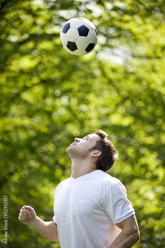 A young man playing with a football