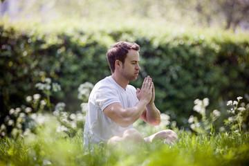 A young man meditating outdoors