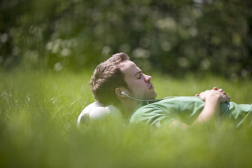 A young man lying on the grass, head resting on a football