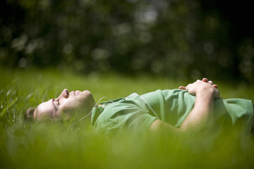 A young man lying on the grass, listening to music