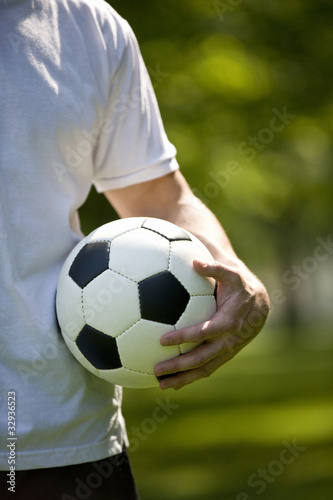 A young man holding a football, close-up