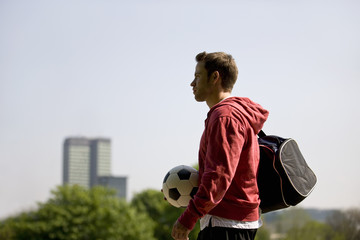 A young man in the park, carrying a football and a sports bag