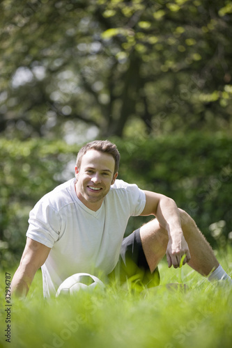 A young man sitting in the park with a football