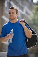 A young man walking, carrying a sports bag and a bottle of water