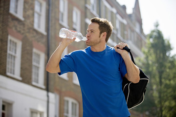 A young man drinking a bottle of water, carrying a sports bag