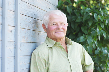 Rentner lehnt an Bretterwand