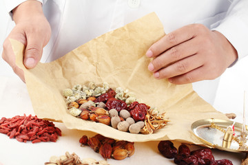 Doctor wrapping Chinese traditional herbal medicine.