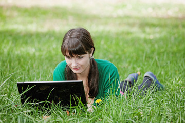 young girl with a laptop in the grass