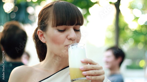 Attractive woman drinking pina colada drink, outdoors