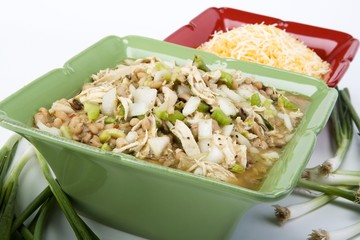 White chicken chili in ceramic dish with cheese & ingredients