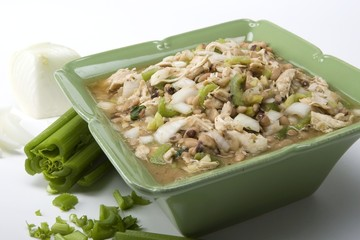 White chicken chili in green ceramic dish and ingredients