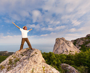 hiker at the top of a rock with his hands up enjoy sunny day