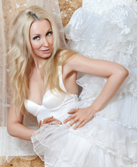 The happy bride tries on a wedding dress..
