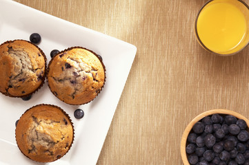 muffin on a sqare plate, orange juice and blueberry