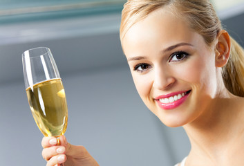 Portrait of happy woman with glass of champagne, at home
