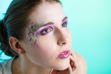 Portrait of young woman with face art