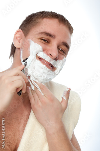 attractive man shaving his face
