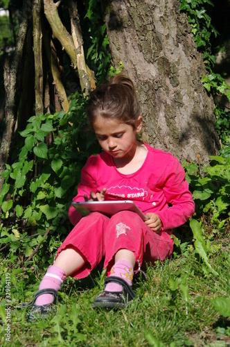 enfant assis au pied d 39 un arbre avec sa tablette tactile de minicel73 photo libre de droits. Black Bedroom Furniture Sets. Home Design Ideas