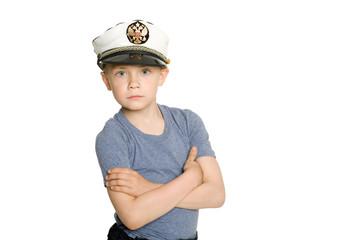 Cute boy in a sea cap. On his cap emblem of Russia.