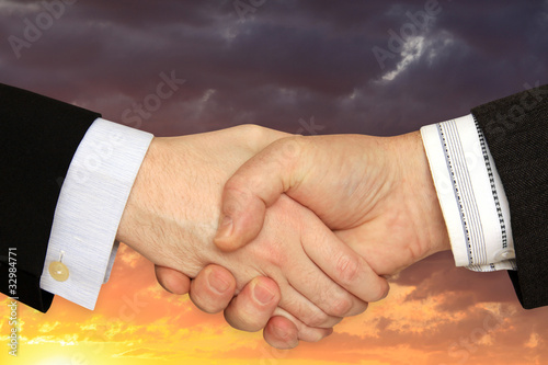Businessmen shaking hands on the dramatically Sky