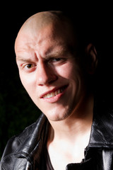 Portrait of a bald gangster in leather jacket