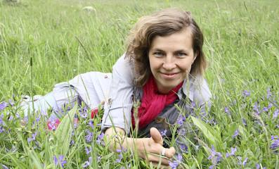 Женщина лежит в цветах и траве и показывает о.к.