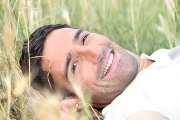 smiling 40 years old man lying down in a field
