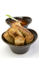 Egg rolls and sweet and sour sauce in a ceramic bowl