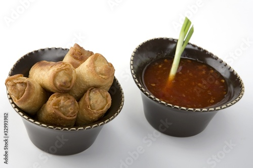 Egg rolls and sweet and sour sauce in a ceramic bow