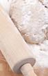Teig ausrollen auf einem Holzbrett