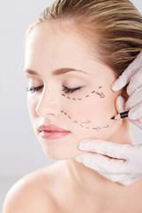 doctor draw correction lines on woman face