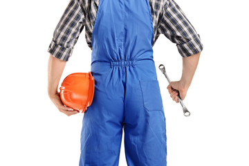 Back view of a repairman in overall holding a wrench and helmet