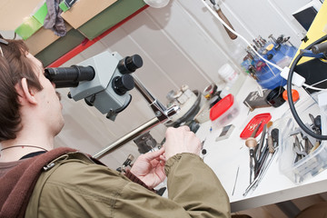 jeweller is working with  microscope