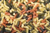 Colorful raw spiral pasta noodles closeup macro
