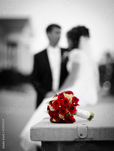 Wedding bouquet with bride and groom on the background