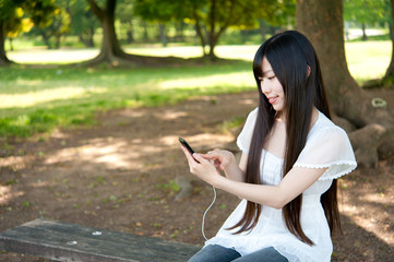 beautiful asian woman using a smartphone in the park