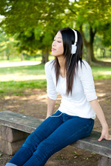 beautiful asian woman listening music in the park