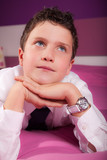 daydreaming teenager boy in dress shirt and tie, lying on bed