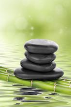 Pierres de basalte zen sur le bambou dans l'eau
