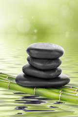 Zen basalt stones on bamboo in water