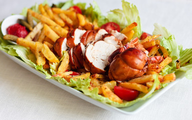 slices of roasted chicken served with french fries and fresh veg