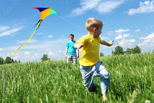 Leinwanddruck Bild father with son in summer with kite
