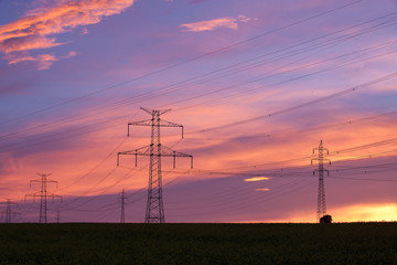 Transmission towers on the hill at pink sunset