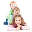 Three smiling kids lying on top of each other