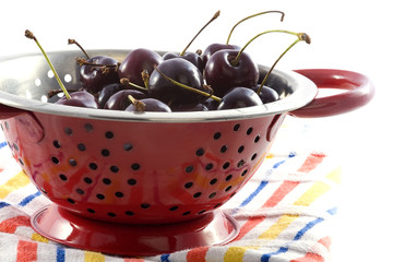 a colander with cherries