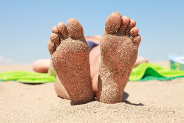 bottom of male feet covered with sand
