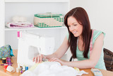 Pretty red-haired female using a sewing machine in the living ro