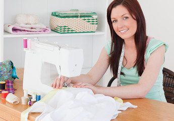 Attractive red-haired female using a sewing machine in the livin