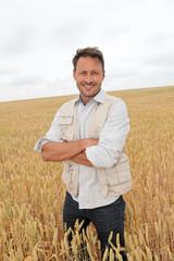 Portrait of handsome man standing in wheat field